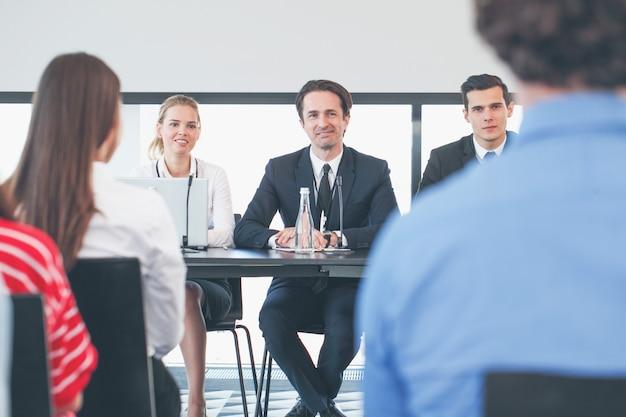 Grupa mówców na spotkaniu biznesowym przy stole z mikrofonami