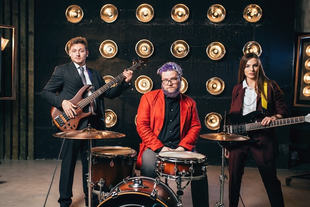 Grupa muzyczna w garniturach na scenie ze światłami