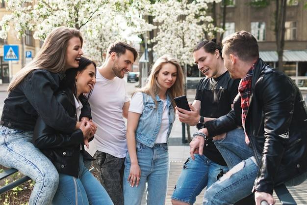 Grupa najlepszych przyjaciół bawi się na ulicy. młodzi ludzie chętnie widzą się podczas spotkania.