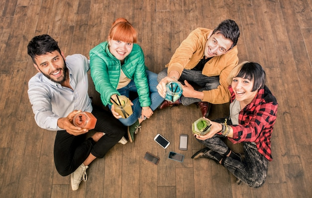 Grupa najlepszych przyjaciół hipster ze smartfonami w nieczysty alternatywnej lokalizacji