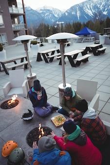 Grupa narciarzy zacierających ręce przy kominku