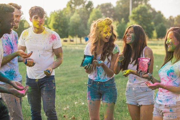Grupa nastolatków bawić się z kolorami przy holi festiwalem w parku