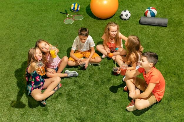 Grupa nastolatków chłopców i dziewcząt siedzących na zielonej trawie w parku