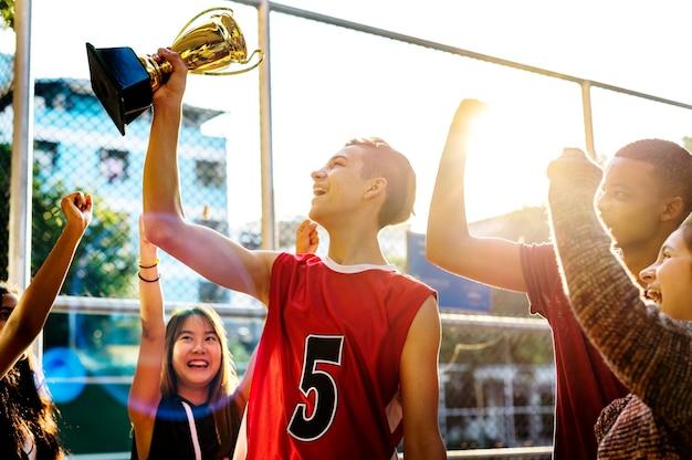 Grupa nastolatków dopingujących trofeum zwycięstwem i koncepcją pracy zespołowej