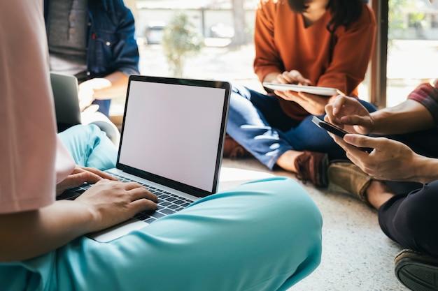 Grupa nastolatków korzystająca z komputera i tabletu do nauki online.