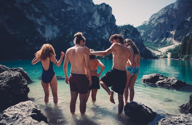 Grupa nastolatków spędzać czas na plaży nad jeziorem