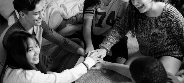 Grupa nastolatkowie w sypialni stawia ich ręki społeczność i temwork pojęcie wpólnie