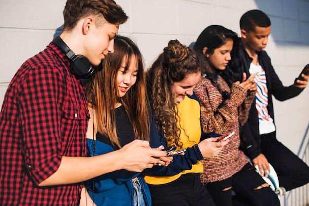 Grupa nastoletni przyjaciele outdoors styl życia i ogólnospołeczny medialny pojęcie