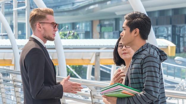 Grupa nauczycieli i uczniów nastolatków spotyka się i rozmawia na zewnątrz.