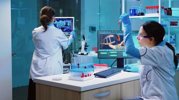 Grupa naukowców w fartuchach laboratoryjnych pracujących w laboratorium podczas badania próbki biochemicznej w probówce i przyrządach naukowych