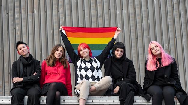 Grupa niebinarnych przyjaciół siedzących i trzymających flagę lgbt