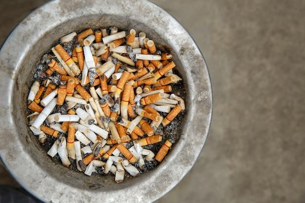 Grupa niedopałków papierosów w brudnym starym koszu