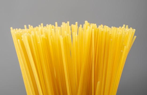 Grupa niegotowanego makaronu spaghetti na szarym tle.