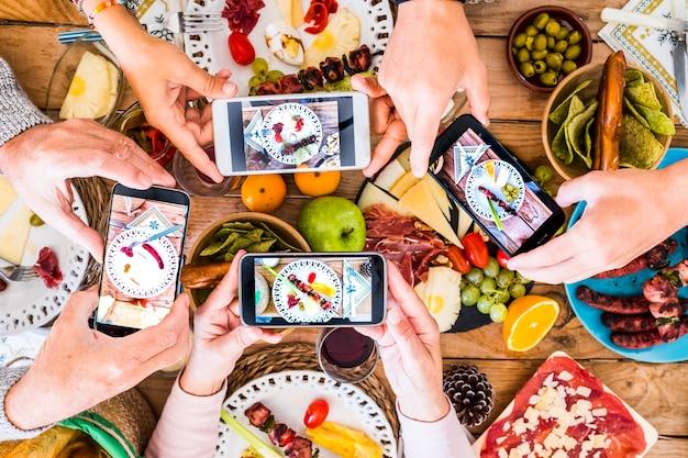 Grupa nierozpoznawalnych przyjaciół lub rodzinnych ludzi rasy kaukaskiej, którzy bawią się razem, robiąc zdjęcia przy swoich potrawach z jedzeniem