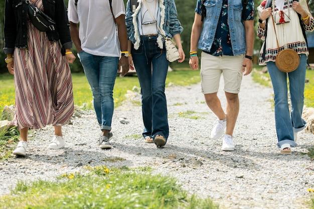 Grupa nierozpoznawalnych przyjaciół w hipisowskich strojach spacerujących razem ścieżką na zewnątrz