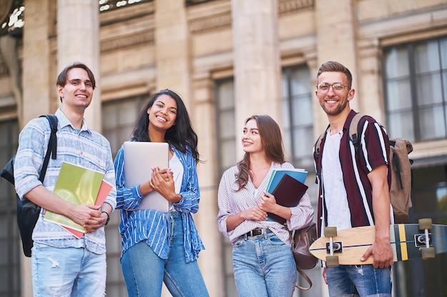 Grupa nowoczesnych nastolatków z laptopem, zeszytami i deskorolką