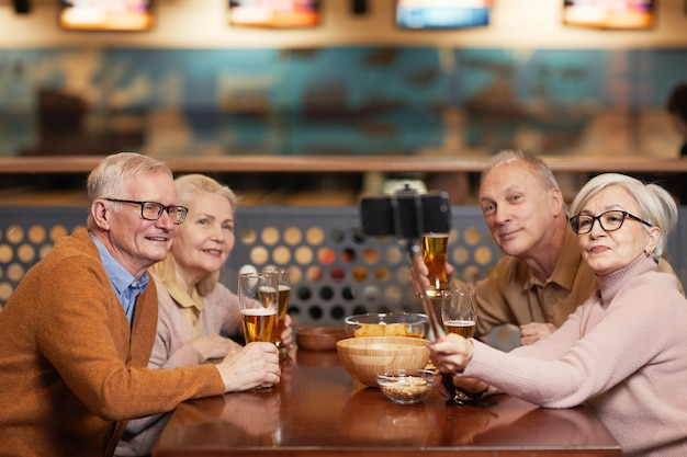 Grupa nowoczesnych seniorów robiących zdjęcie selfie podczas picia piwa w kręgielni i cieszenia się wieczornym wyjściem z przyjaciółmi, kopia przestrzeń
