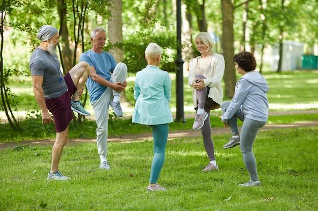 Grupa nowoczesnych starszych ludzi spędzających słoneczny poranek w parku robi ćwiczenia rozciągające