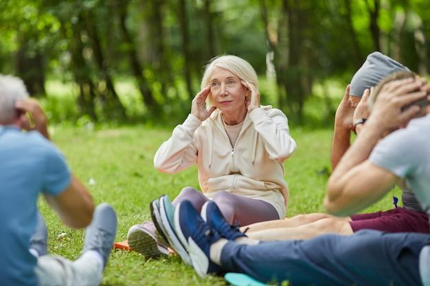 Grupa nowoczesnych starszych ludzi zebranych razem w parku siedzi na matach na trawie robi ćwiczenia rozciągające szyi i relaksujące