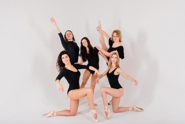 Grupa nowoczesnych tancerzy baletowych w czarnych body w białym studio
