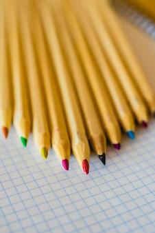 Grupa ołówków ułożonych na papierze milimetrowym.