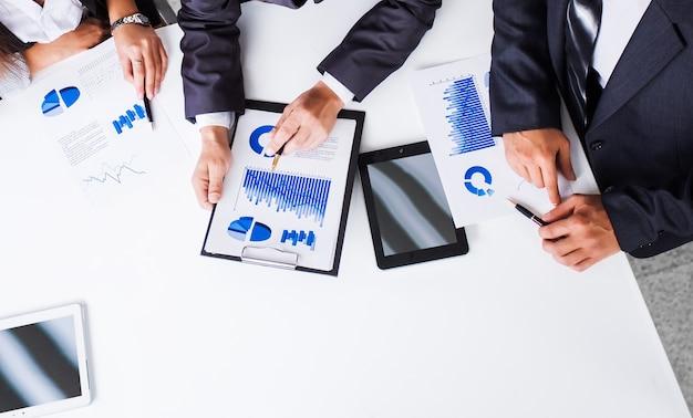 Grupa odnoszących sukcesy biznesmenów. dyskusja o wykresach i grapie