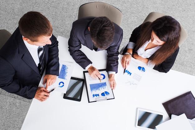 Grupa odnoszących sukcesy biznesmenów. omówienie wykresów i wykresów przedsiębiorstwa.