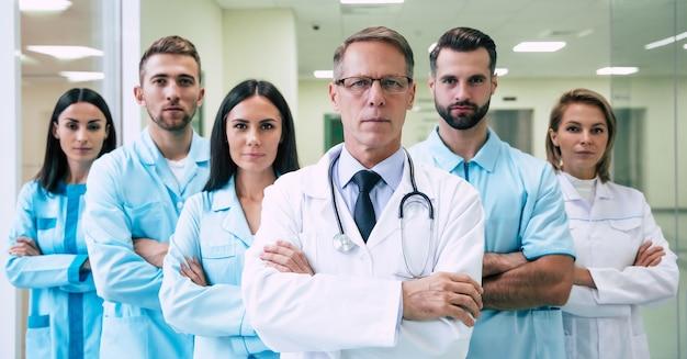 Grupa odnoszących sukcesy i pewnych siebie współczesnych lekarzy pozuje i patrzy w kamerę na korytarzu szpitalnym