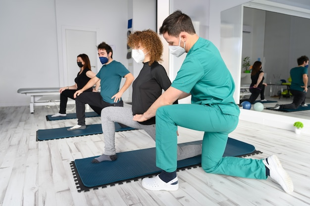 Grupa osób na matach do jogi w asyście fizjoterapeuty w poradni rehabilitacyjnej.