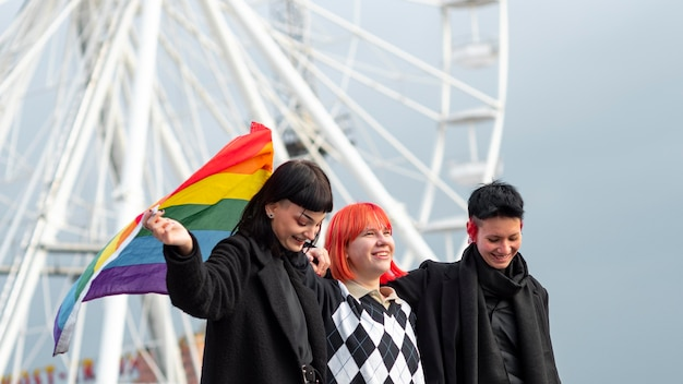 Grupa osób niebinarnych z flagą lgbt
