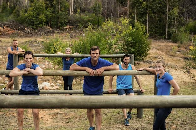 Grupa osób opierających się o płotki podczas treningu z przeszkodami