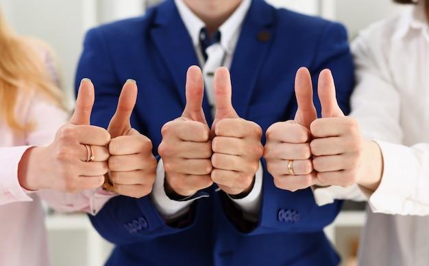 Grupa osób pokazuje ok lub zatwierdzenie kciukiem