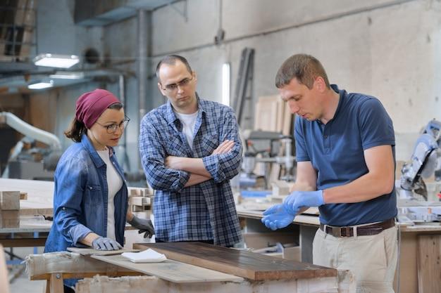 Grupa osób pracujących w warsztacie stolarskim