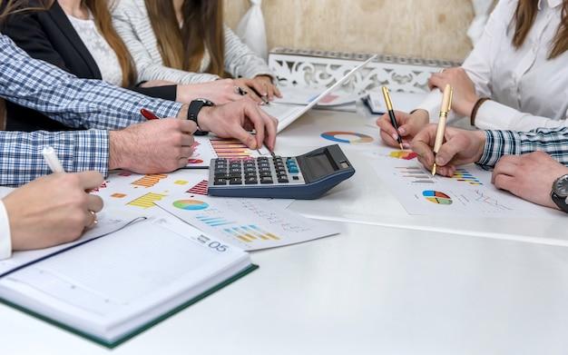 Grupa osób pracujących z wykresem biznesowym w biurze