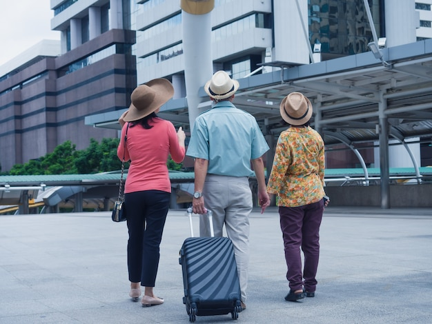 Grupa osób starszych podróżuje po mieście, starszy mężczyzna i starsza kobieta rozglądają się i spacerują po mieście