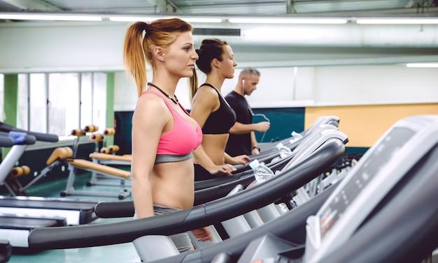 Grupa osób trenujących na bieżniach w centrum fitness