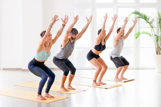 Grupa osób wykonujących utkatasanę lub krzesło podczas ćwiczeń jogi w jasnej i przestronnej sali gimnastycznej
