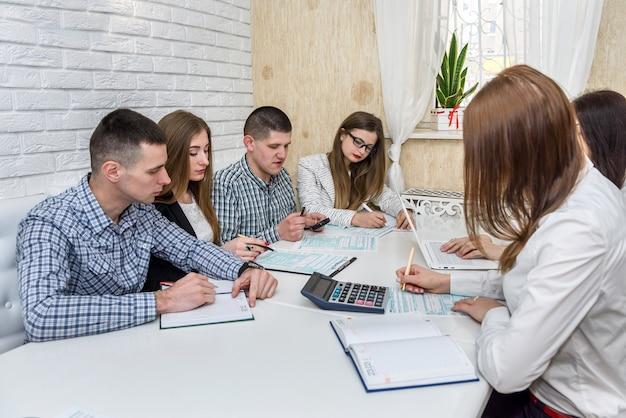 Grupa osób wypełniająca formularz w biurze
