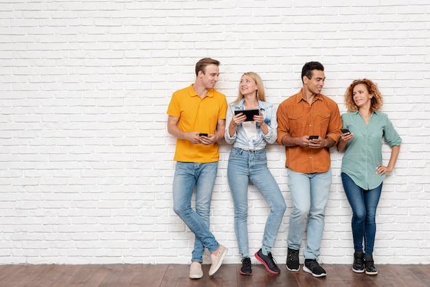 Grupa osób z urządzeniami elektronicznymi