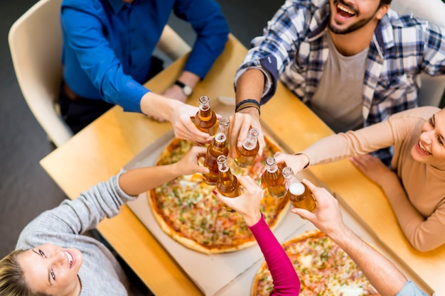 Grupa oung ludzie je pizzę i pije cydru w nowożytnym wewnętrznym widoku od above
