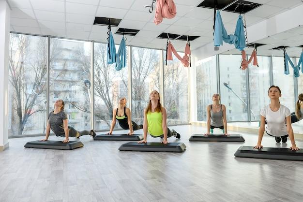 Grupa pań, wykonywanie ćwiczeń w siłowni