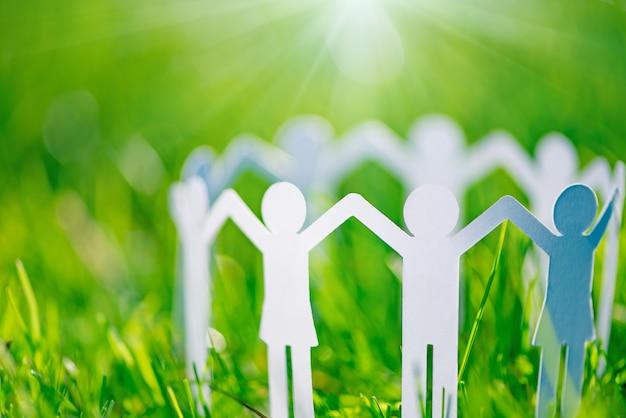 Grupa papierowi ludzie trzyma ręki wpólnie. pojęcie pomocy społecznej w grupie. koncepcja zespołu
