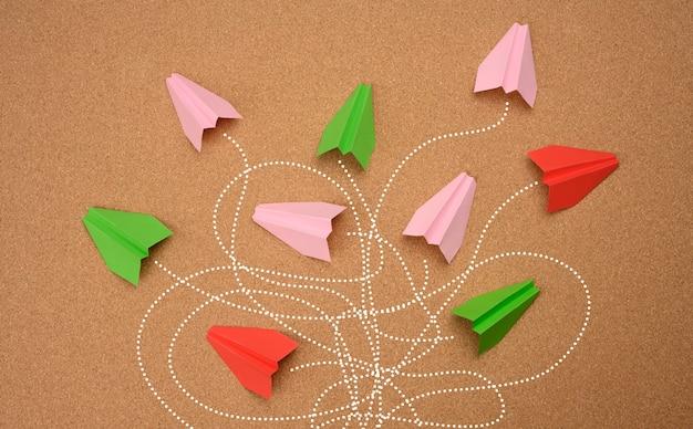 Grupa papierowych samolotów z długimi splątanymi ścieżkami na brązowej powierzchni. koncepcja silnego lidera z niezwykłym myśleniem, szybkim podejmowaniem decyzji. znalezienie optymalnego i prostego rozwiązania w biznesie