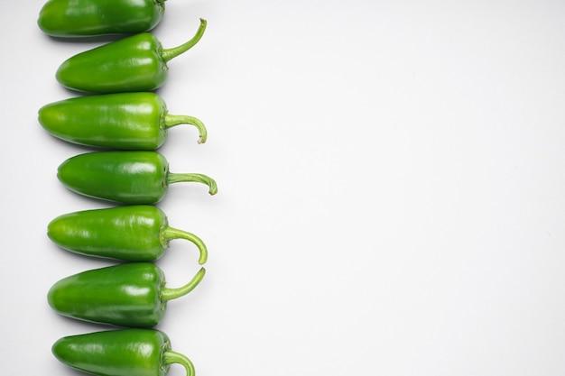 Grupa papryki jalapeno na białym tle, miejsca na tekst, widok z góry. zielona papryczka chili.