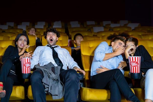 Grupa par osób oglądających film czuje się przerażająco i przerażająco na siedzeniach w kinie