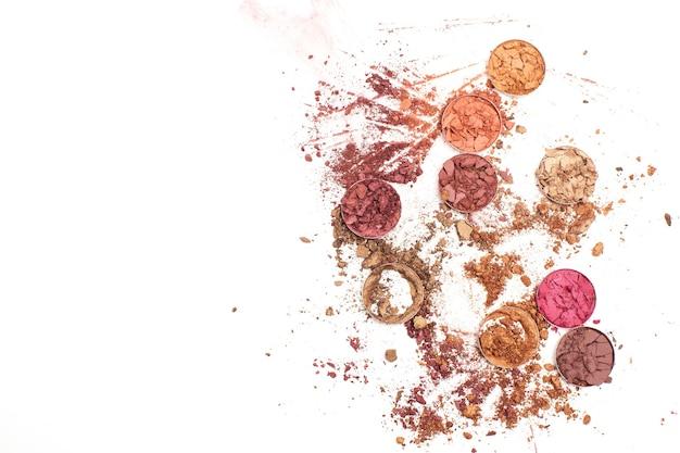 Grupa pękniętych złotych i różowych cieni do powiek na białym tle. miejsce na tekst