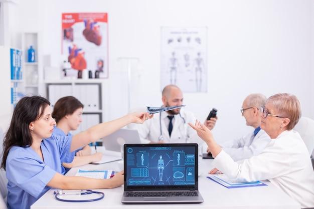 Grupa personelu medycznego omawiająca w sali konferencyjnej szpitala na temat radiografii pacjenta. ekspert kliniczny terapeuta rozmawiający z kolegami o chorobie, specjalista od medycyny