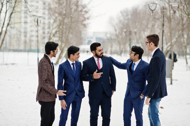 Grupa pięciu indyjskich biznesmenów w garniturach pozuje na zewnątrz i prowadzi dyskusję w zimowy dzień w europie.