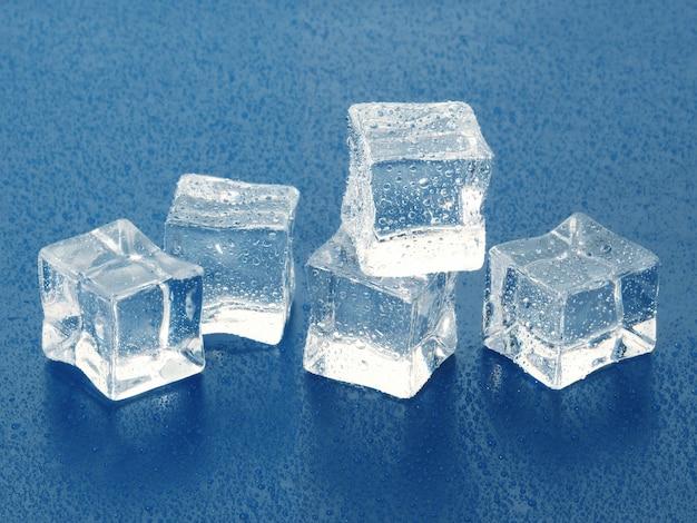 Grupa pięciu kostek lodu mokrych na jasnoniebieskiej powierzchni