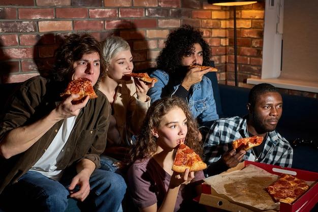 Grupa pięciu młodych przyjaciół siedzi na kanapie w domu, jedząc pizzę, oglądając telewizję, ciekawą komedię filmową. koncepcja przyjaźni, jedzenia i wypoczynku